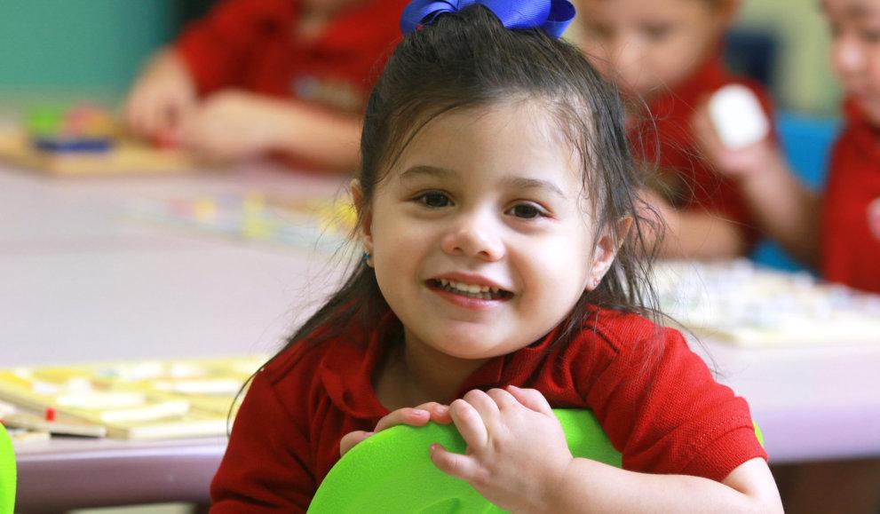 kid wearing blue ribbon smiling