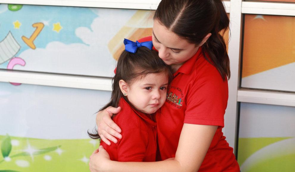 teacher comforting crying kid