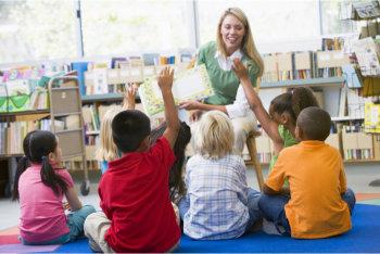 a teacher and children raising their hand